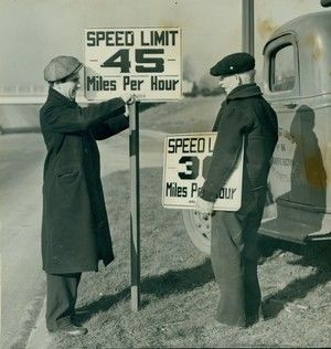 City employees placing new signs marking the raising of the speed limit from 30 to 45 miles per hour between Skinker and Vandeventer on the Superhighway. 13 January 1938.