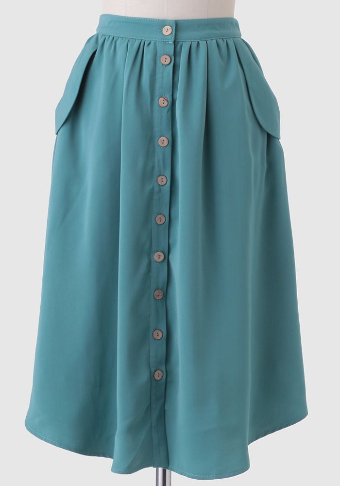 Crafted in a stunning teal shade, this incredibly smooth skirt is designed with faux wood button closures down the front and two side pockets.