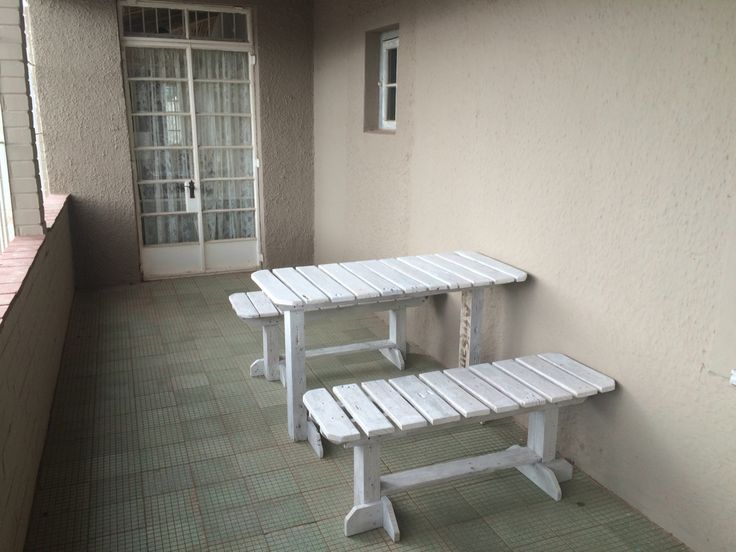 Pallet table and benches on the front stoep (pirch or verandah). Also been washed white. Road to the left of pic and its great to sit and drink coffee and greet the passers by....