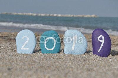 Happy New Year 2019 on stones with coastal background
