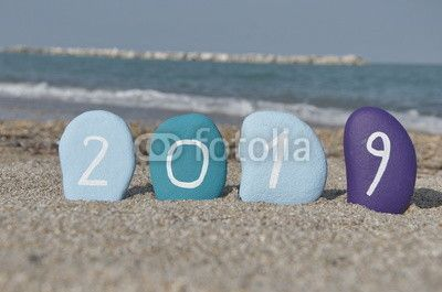 Happy New Year 2019 on stones with coastal background