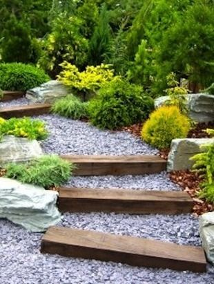 Add some visual interest and practical purpose to a sloped garden landscape by creating a gavel-stepped walkway. Pea gravel and new or salvaged wood beams are all that you will need to create one like this. Simply level out the grade, or create steps with the beams and fill in with gravel.