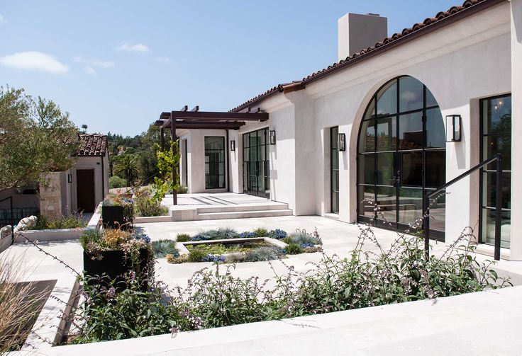 COLC: Light fixtures, planters, large arched openings, steel trellis.  Spanish Modern
