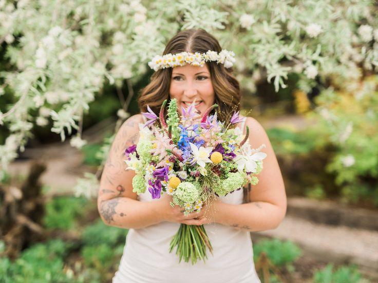 Bruden har en somrig och yvig bröllopsbukett med bland annat veronica, daggkåpa, delfinium, viburnum, klematis, luktärt och akleja i. Floristen har skapat en bukett med säsongens blommor som får en att tänka på en vacker blomsteräng.