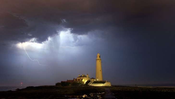 A stormy scene above a lighthouse: The Met Office has issued severe weather alerts, warning of potential power cuts, damage to buildings and disruption (Owen Humphreys/PA)