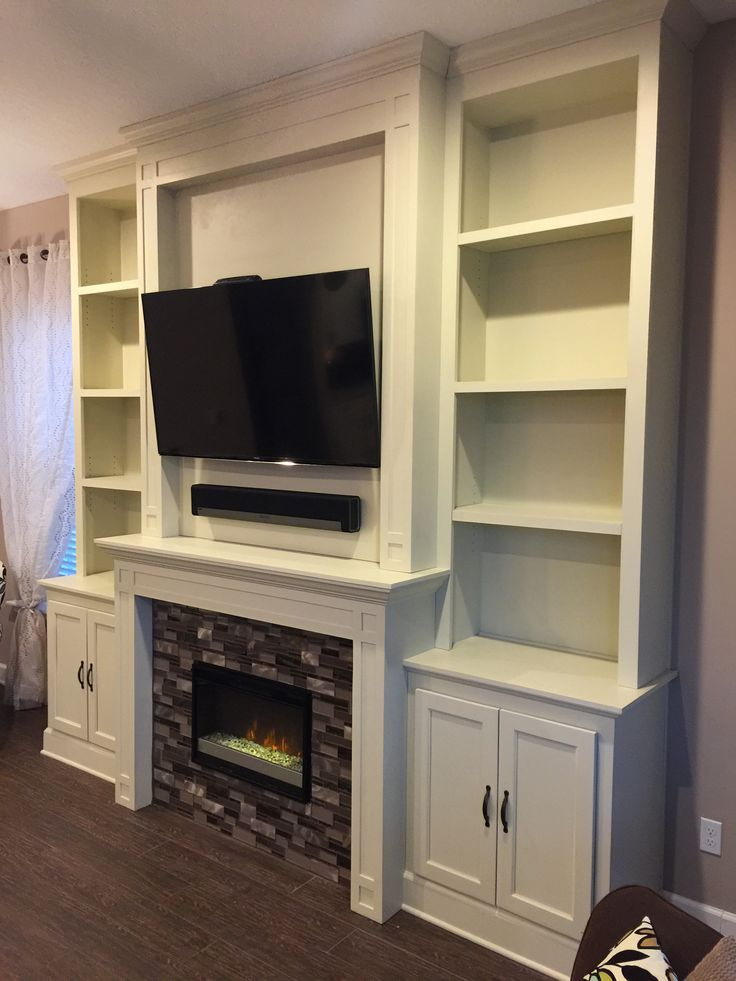 Custom fireplace, electric fireplace, tile surround, built in bookcases, tv over fireplace, surround sound