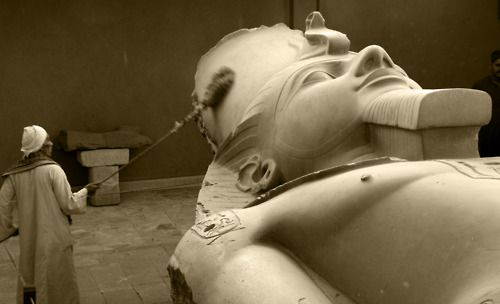 Museum worker in the process of cleaning the Ramses II colossus