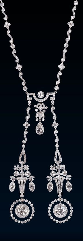 An Edwardian platinum and diamond lavallière, probably English, circa 1910. Platinum millegrain and diamond Lavallière, the chain composed of a sequence of quatrefoils, collet set diamonds and S shaped links caught together by a curved bar with Greek fret from which hangs a diamond chain  while to each side the neck chain terminates in twin openwork baskets of flowers finished below with two round diamond in open circles. #Edwardian