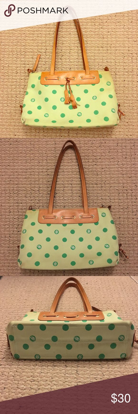 Dooney and Burke polka dot shoulder bag Pre-owned Dooney and Burke polka dot shoulder bag. Very roomy and you can easily fit a lot of your personal belongings! The fun, colorful design will surely turn heads and brighten up your closet!  Inside are two equally sized pocket compartments. The bag zips fully closed. People magazine illustrated there for size comparison.   There are scuff marks on the bottom four corners, light brown staining at the top near the zipper, and slight black marks on…