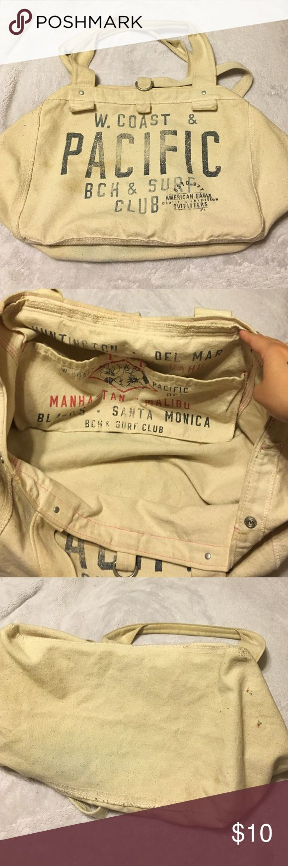 American Eagle Canvas Tote Bag Cream canvas bag with blue lettering. Unsnaps at top to make bigger. Two pain spots on bottom (3rd picture). But otherwise good condition. American Eagle Outfitters Bags Totes
