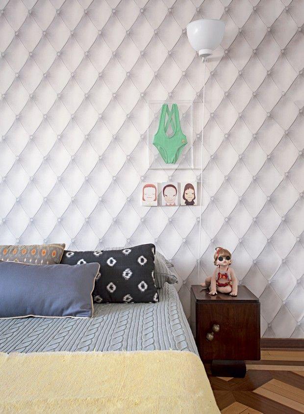 Quarto   O efeito capitonê do papel de parede dá sensação de conforto e dispensa cabeceira. No criado-mudo, boneca de porcelana numerada, e, acima dele, maiô da infância e quadrinhos de Yoshitomo Nara. Na cama, colcha de tricô da Mundo do Enxoval