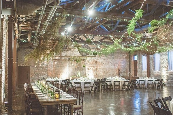 string lights and greenery hangs over reception in industrial venue