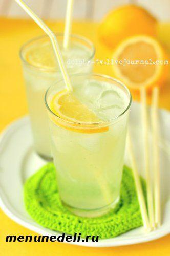 Готовый лимонад приготовленный в домашних условиях в стакане с долькой лимона и трубочкой
