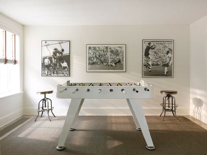 Vintage style game room featuring vintage sports memorabilia over vintage industrial bar stools as well as white foosball table.