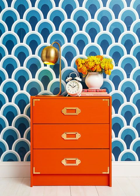 Recreate the classic design by painting on two to three coats of a bold, high-gloss hue (we love vibrant orange!), then attaching gold or brass corner hardware and pulls. Wallpaper ($35 per roll, chasingpaper.com). Vase ($24, wolveswithin.com). Clock ($30,westelm.com). Books (anthropologie.com). Paint, Inferno by Behr. Pulls ($35 each, rejuvenation.com). Corners ($6 for four, amazon.com).