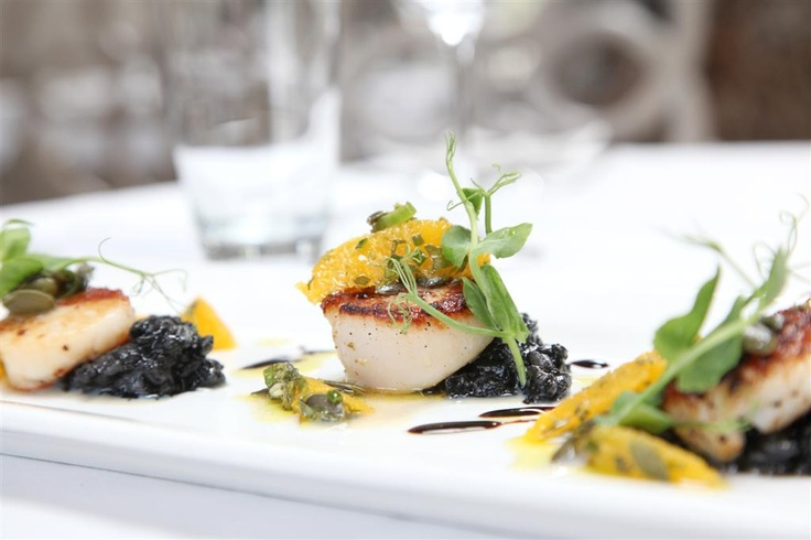 Pan fried scallops with squid ink risotto with herb-orange salsa