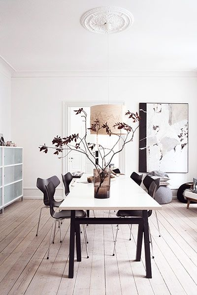 Dining room table by SUP Design (from Design Nation), with Arne Jacobsen's Grand Prix chairs from Aram. The smoky vase is from By Nord, and the birch pendant by Cathrine ­Kullberg is from Heal's.
