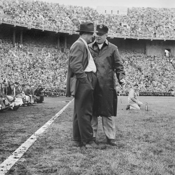 "Football History! Photo appears to show Ohio State head football coach Woody Hayes (left) confering with an unidentified assistant coach in Ohio Stadium against the Iowa Hawkeyes. Ohio State won, 20-14. Wayne Woodrow ""Woody"" Hayes coached the Buckeyes from 1951-1978, compiling an overall record of 205-61-10, with 13 Big Ten titles, four Rose Bowl wins (eight appearances) and five national championships. He was inducted into the College Football Hall of Fame in 1983. Photo October 16, 1954."