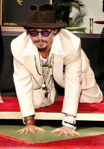 Johnny Depp dips his hands and feet in concrete in the courtyard of Mann's Chinese Theatre on September 16, 2005 in Hollywood, California.