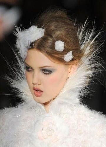 Chanel fashion: Chanel's symbol camellias and pure white feather nearly becomes one. Silver threads, tweed and feathers blend together make supermodel Lindsey Wixson look like an angel.