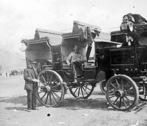 1910-1920? Coach used by Wolcott School at annual field day Elitch Gardens.  Men pose with a touring wagon or omnibus used by the Wolcott school in North Denver.features roof seats and lanterns.