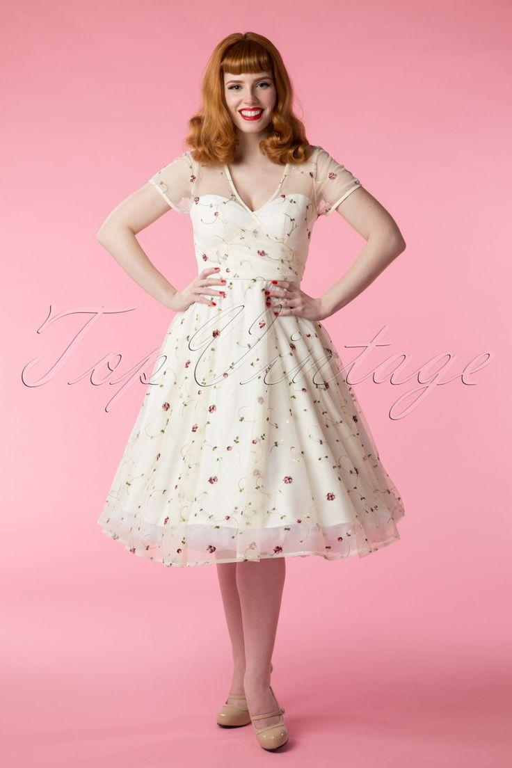 Deze50s Nina Floral Swing Dress in Ivoryvan Collectif Clothing is super romantisch!  De perfecte jurk voor een zomerbruiloft of een andere speciale gelegenheid waar je elegant en lieflijk voor de dag wilt komen! De top heeft speelse korte mouwtjes, een subtiele V op de rug eneen prachtige overslag voor een mooi classy decolleté. De bovenste laag van de jurk is gemaakt van doorschijnend ivoorkleurig tule bezaaid met romantische geborduurde bloemetjes en de onderjurk z...
