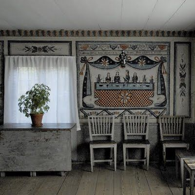 An old Swedish cottage with walls painted in traditional folk art in blues, greys and red.