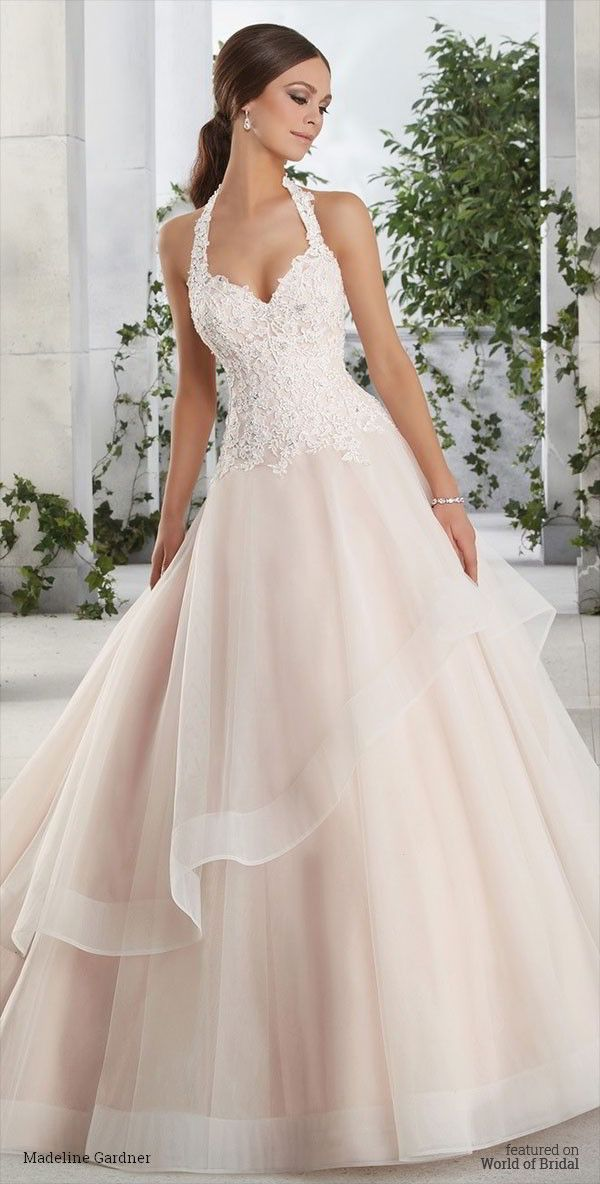 A crystal and pearl beaded halter neck bodice with lace appliques on a tulle ball skirt with asymmetric overlay