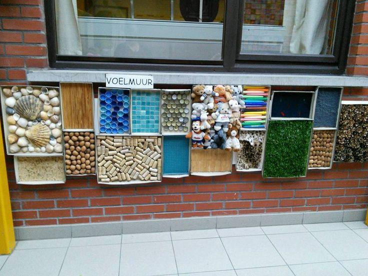 Een voelmuur, wat een leuk idee! Ik zou de dozen alleen vervangen door houten kistjes.
