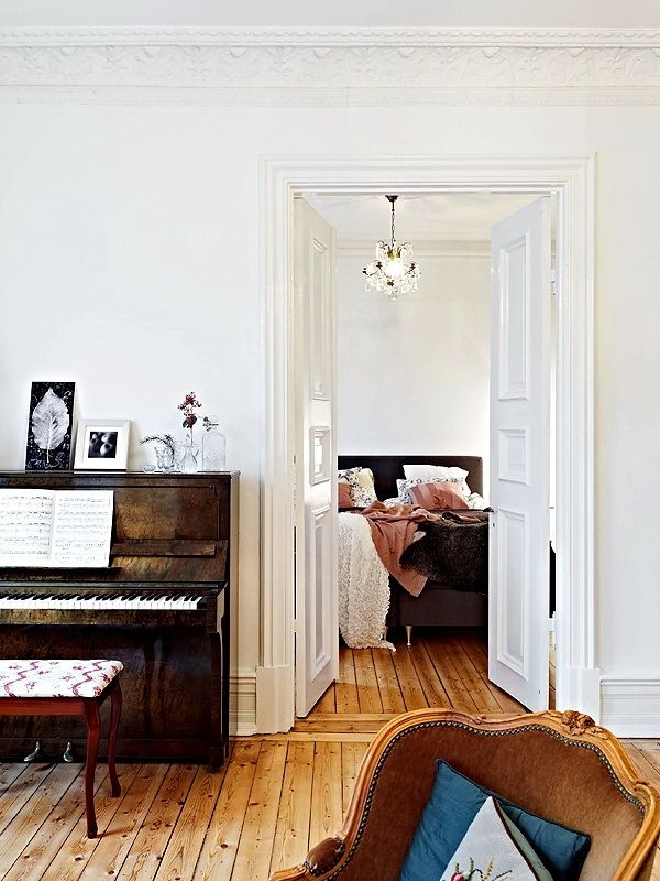 Love the old piano & mismatched (reddish) piano stool. Also love the floors and high ceilings with moulding. And those doors!