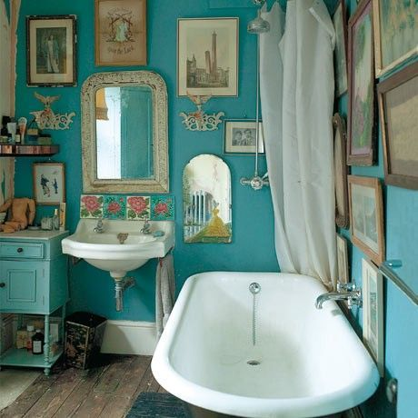 Cor turquesa e quadros surpreendem no banheiro.