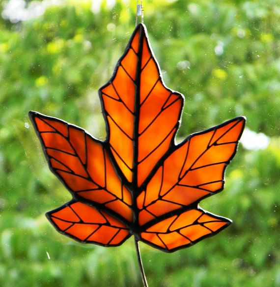 "Stained glass maple leaf. Approximately 5"" overall. Leaf is constructed of Golden Orange variegated stained glass with wire overlay to resemble the veining in a real leaf. Leaf is assembled using the Tiffany Copper Foil method. Black patina has been applied to give this a rich finish look. Several inconspicuous hanging loops are added on the back for more hanging positions. Suction cup for hanging is included in price. $25"