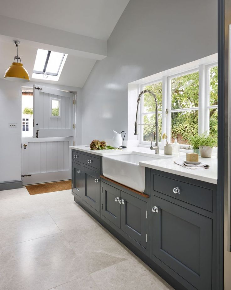 Martin Moore are increasingly being asked to incorporate back kitchens into their bespoke designs. The back kitchen shown here is painted in Farrow & Ball 'Downpipe'. The worktop and upstands in 'Organic White' Caesarstone. martinmoore.com