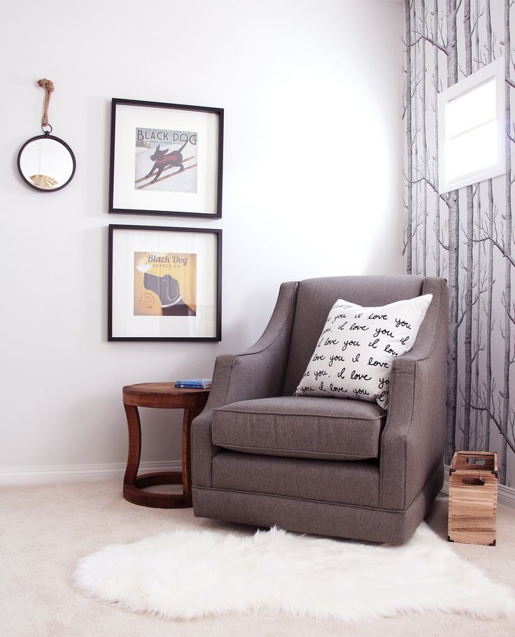 nursery with stacked art, tree wallpaper and rocking chair