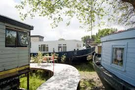 The site, which is now heavily polluted, will feature imaginatively retrofitted houseboats placed around a winding wooden walkway and surrounded by an undulating landscape of soil-cleaning plants.