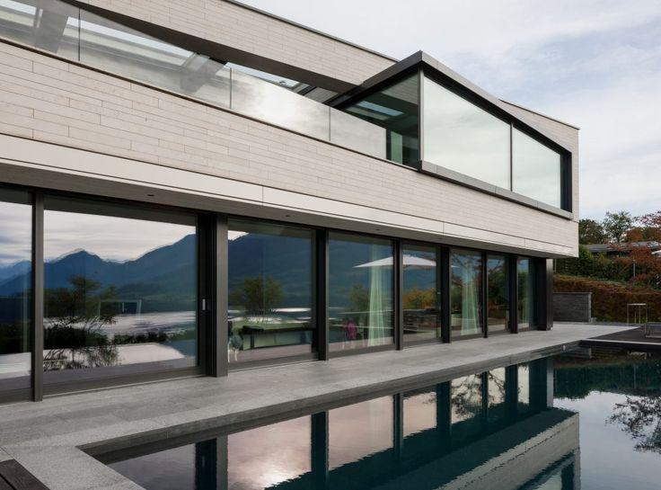 Naturstein Schwimmbecken gespiegelt in den Fenstern