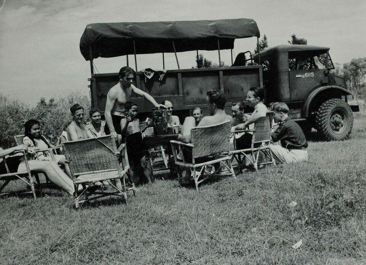 Nederlandse militairen en Indische kinderen ontspannen naast een legervrachtwagen bij de badplaats kampong Tjilintjing, [vlak na de eerste politionele actie, augustus 1947], West-Java Indonesië.