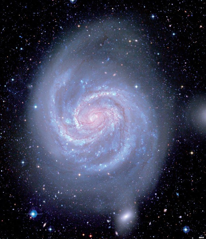 Large spiral galaxy Messier 100 appears face-on to viewers on Earth. The spiral arms make wavelike patterns in the rotating disk of stars, gas and dust. - Credit: Canada-France-Hawaii Telescope/Coelum