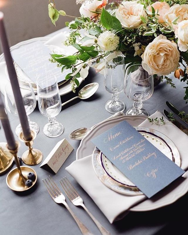 A wedding doesn't have to be neutral to be elegant. This design by @tebbeyandco, with florals by @thegardengateflowerco, shows us how a combination of stormy blues and plums can pair with summery peaches to create the elegant tablescape of our dreams. Photo: @taylorandporter | Calligraphy: @claire_gould1 | Venue: @enysweddings #elegantwedding #weddingdecor #weddingflowers #centerpiece #calligraphy