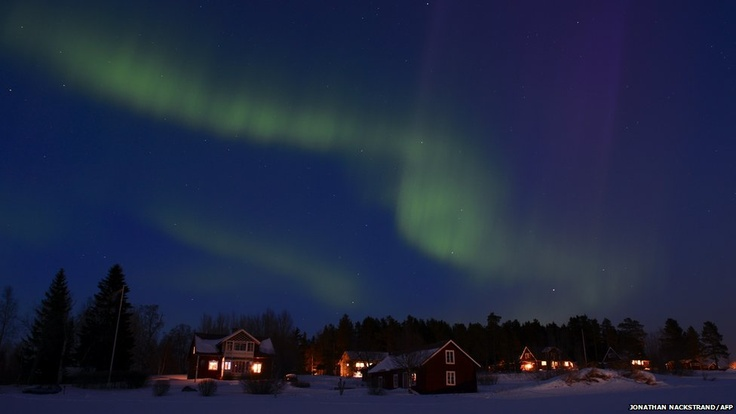 The aurora borealis lights up the sky at twilight between the towns of Are and Ostersund in Sweden