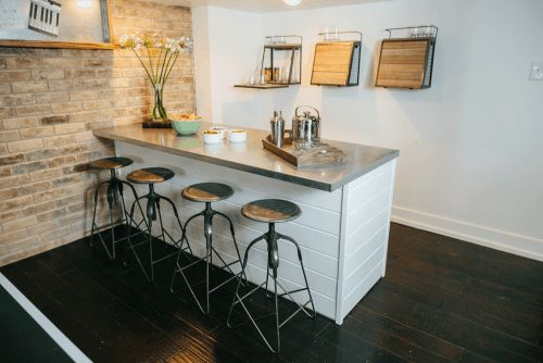 In the game room, Chip and Joanna updated the bar area to give it a clean look. The existing brick wall added some warmth to the space and the metal accents. Joannabrought in a ping pong table for the room, promising to provide a great source of entertainment for their kids.