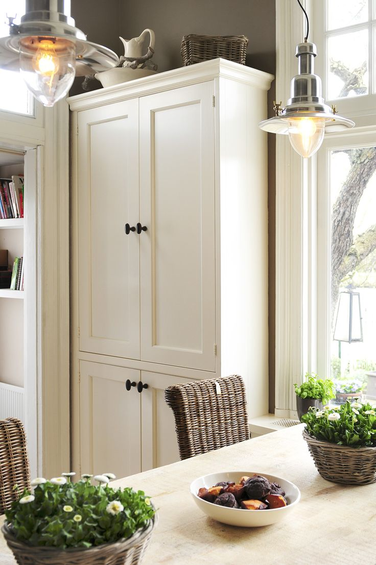 Love the cupboard and dark wicker chairs with white table
