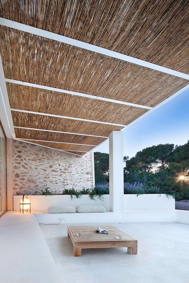 para la casa de playa: detalle lounge exterior delante  del vestíbulo con pérgola metálica de plementería de cañas