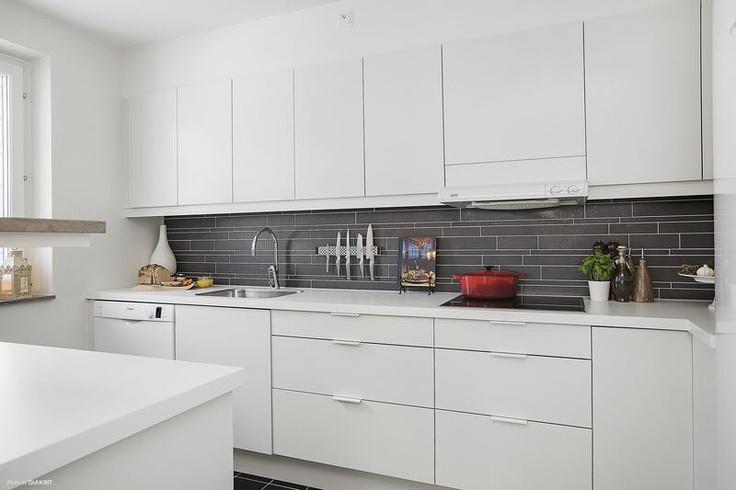 Klassiskt kök i vitt och grått med italiensk stavmosaik och push to open-köksskåp
