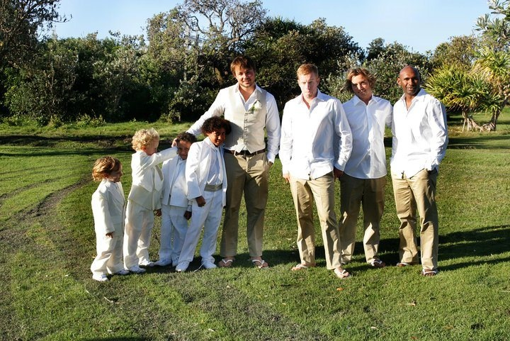 The groomsmen in beige suit pants with white shirts, the ring bearers in white suits and the groom in a beige vest and suit pants with a white shirt.