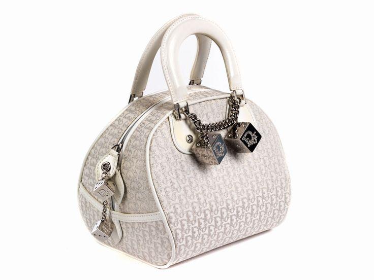 """Ca. 19 x 20 x 15 cm. Handtasche aus Stoff in Cremeweiß verziert mit dem """"Dior"""" Monogramm in Silber, zwei Handgriffen, Reißverschluss und silberfarbenem..."""