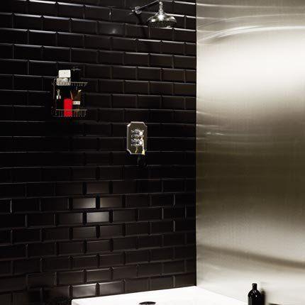 Avec des murs en carreaux de métro noirs et de l'inox brossé