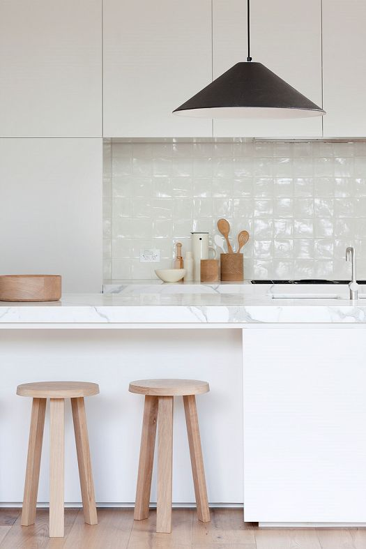 Soft white tile + white marble kitchen with wide plank wood floors