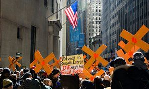 A divest from fossil fuel demonstration in front of the New York stock exchange, Wall Street, New York.