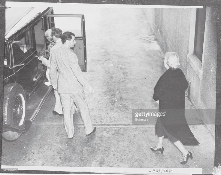 As Death Claimed Jean Harlow. Mrs. Jean Bello, mother of Jean Harlow, being helped into a car by her divorced husband Marino Bello, as they left Good Samaritan Hospital, Los Angeles, a few minutes after the death of the famous blonde star. Howard Strickling, of MGM's publicity staff, is the man in the light suit. The lady at right, walking toward the car, is Miss Jetty Chadsey, Aunt of the actress.